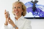 Professorin Dr. Meike Stiesch mit einem vergrößerten Modell eines Zahnimplantats.