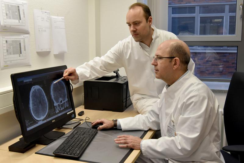 Studienleiter Prof. Dr. Ramón Martínez-Olivera (vorne) mit Oberarzt Dr. Bogdan Pintea bei der Befundung einer Computertomografie des Kopfes nach einem Schädel-Hirn-Trauma