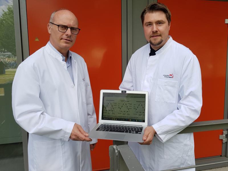 Prof. Dr. Markus M. Nöthen (links) und Dr. Andreas Forstner mit einer Abbildung, wie verschiedene psychische Erkrankungen genetisch zusammenhängen.