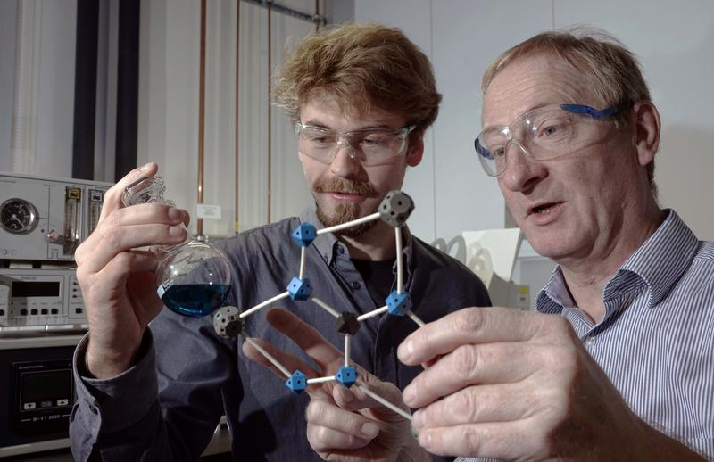 PhD student Benjamin Kintzel (l.) and Prof. Dr Winfried Plass discuss a molecule they have developed, that may possibly be used in a quantum computer.