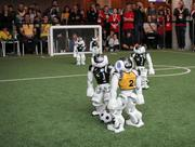 Two robots arrive at the ball and both try to gain possession. The photo was taken during the semifinal match against rUNSWift at RoboCup 2019 in Sydney.
