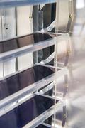 The slats of the solar thermal venetian blind (STVB) absorb the incident solar radiation. The heat is transferred to the collecting channel via heat pipes and an aluminum adapter.
