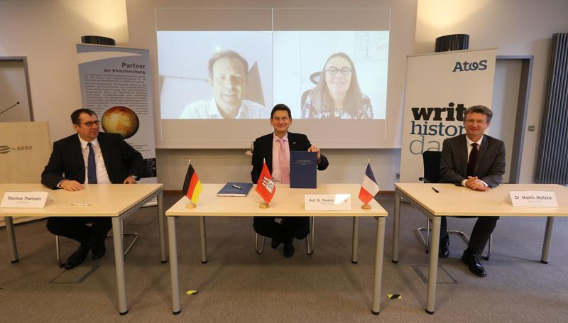 From left to the right: Thomas Theissen, Atos in Germany, Prof. Thomas Ludwig, DKRZ, and Dr. Martin Matzke, Atos Central Europe. Connected via video conference: Philippe Miltin, and Agnès Boudot, both Atos.